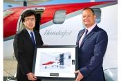 Howard Povey accepts the keys to HondaJet M-HNDA from Michimasa Fujino, President and CEO of Honda A